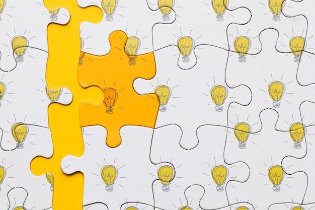 Puzzle piatto laico con lampadine su sfondo giallo