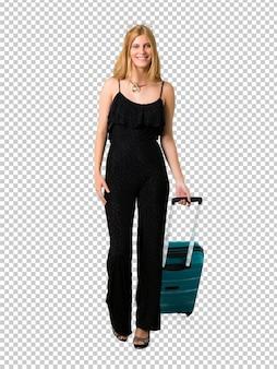 Ragazza bionda che viaggia con la sua valigia a piedi. gesto di movimento