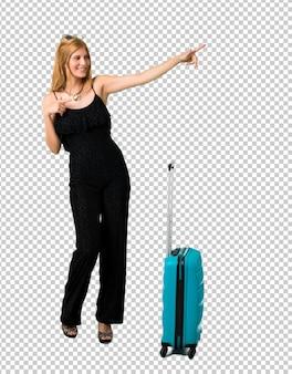 Ragazza bionda che viaggia con la sua valigia che indica il dito sul lato e che presenta un prodotto