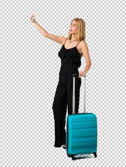Ragazza bionda che viaggia con la sua valigia prendendo un selfie con il cellulare