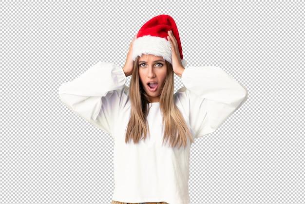 Ragazza bionda con il cappello di natale con espressione facciale di sorpresa