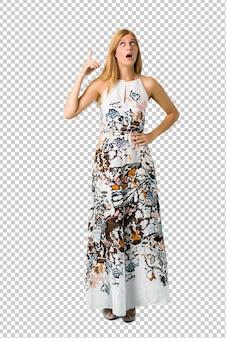 Ragazza bionda in un abito estivo in piedi e pensando un'idea che punta il dito verso l'alto