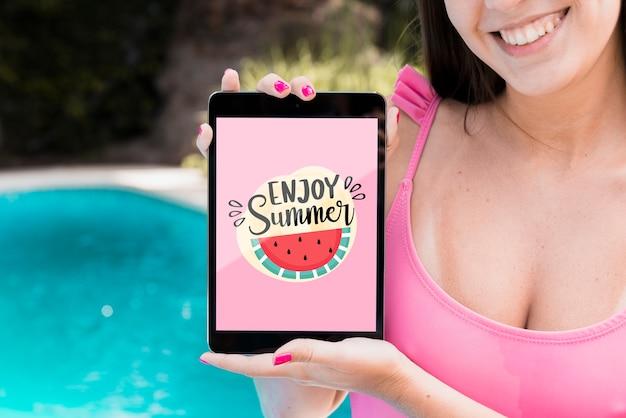 Ragazza che presenta tablet mockup accanto alla piscina