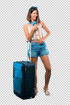 Ragazza che viaggia con la sua valigia che indica il dito sul lato e che presenta un prodotto