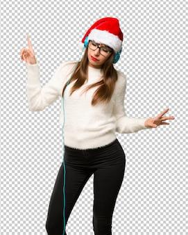 Ragazza con celebrando le vacanze di natale ascoltando musica con le cuffie e ballare