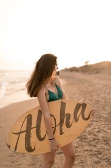 Ragazza con tavola da surf in spiaggia
