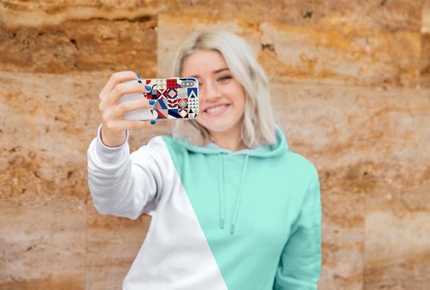 Ragazza di smiley con felpa con cappuccio prendendo selfie