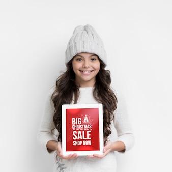 Ragazza di smiley con foglio di carta per i saldi invernali