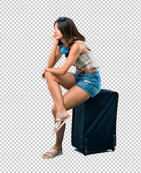 Ragazza stanca che viaggia con la sua valigia