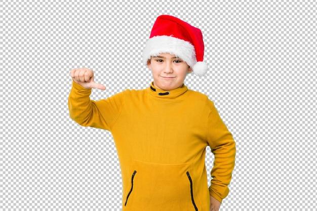 Ragazzino che celebra il giorno di natale indossando un cappello santa mostrando un gesto di antipatia, pollice verso il basso. concetto di disaccordo.