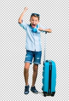 Ragazzino con occhiali da sole e cuffie che viaggiano con la sua valigia per celebrare una vittoria