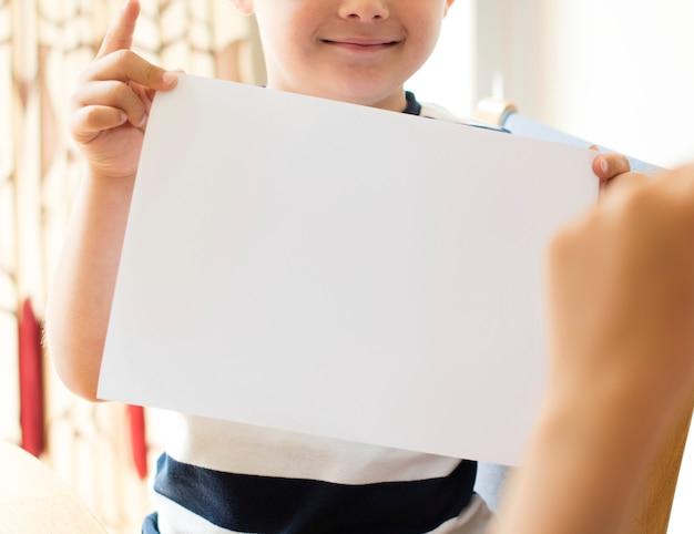 Ragazzino con un mockup di carta bianca