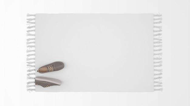 Realistisch wit tapijt met een paar schoenen in bovenaanzicht