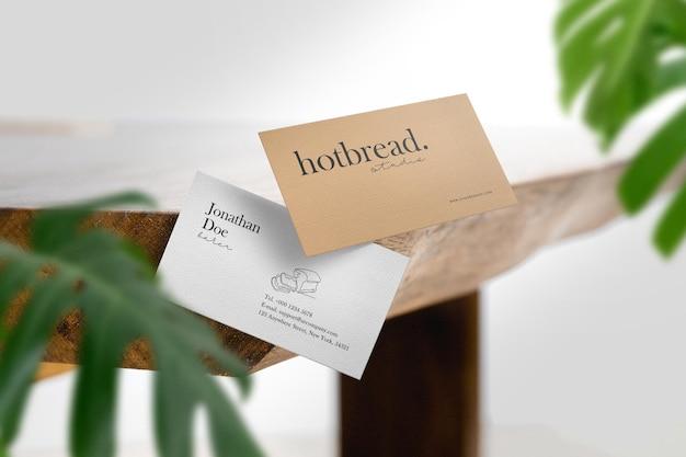 Reinig de minimale houten tafelzijde van het visitekaartje met bladeren