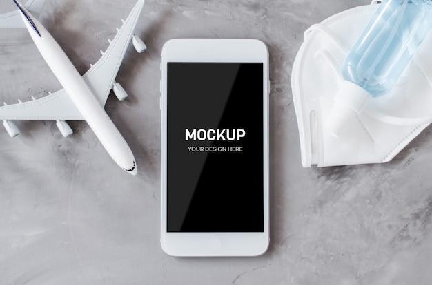 Reisplanning concept en coronavirus. mock up van smartphone met vliegtuigmodel gezichtsmasker en desinfecterende spray.