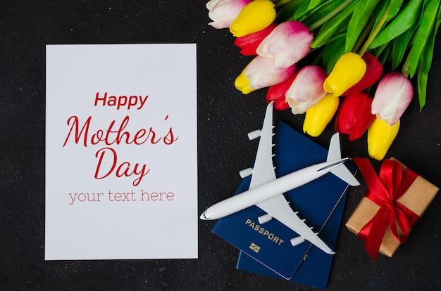 Reisplanning met vliegtuigmodel, paspoorten, blanco papier, boeket tulpen en geschenkdoos