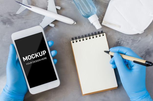 Reisplanningsconcept, coronavirus en quarantaine. handen in wegwerphandschoenen houden smartphone en schrijven in notitieblok. bespotten met kopie ruimte. vliegtuigmodel, gezichtsmasker en handdesinfectiespray.