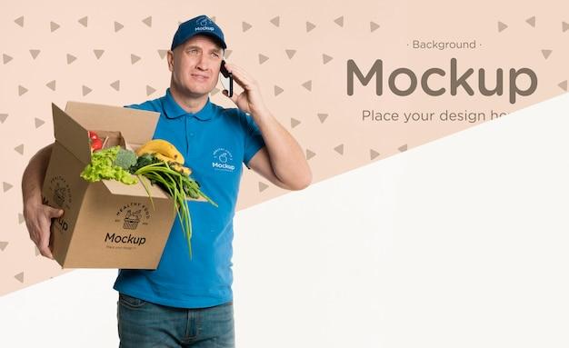 Repartidor sosteniendo una caja con verduras mientras habla por teléfono