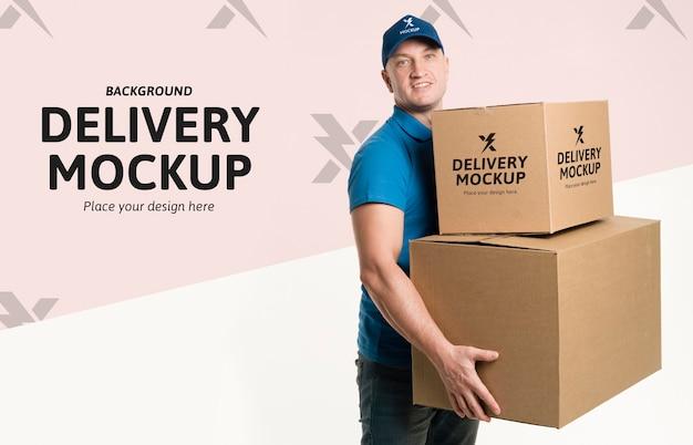 Repartidor sosteniendo un montón de cajas con maqueta de fondo