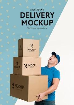 Repartidor de vista frontal sosteniendo un montón de cajas