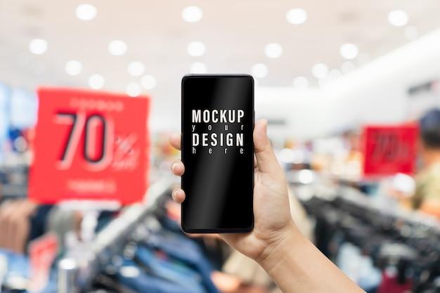 Resumen maqueta teléfono móvil con tienda de ropa borrosa
