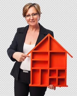 Retrato de una empresaria madura sosteniendo una forma de casa