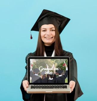 Retrato de estudiante sosteniendo portátil con maqueta