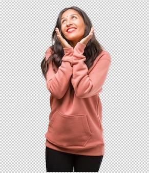 Retrato de fitness joven india sorprendida y conmocionada, mirando con los ojos muy abiertos, entusiasmada por una oferta o por un nuevo trabajo, gana el concepto