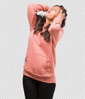 Retrato de fitness joven mujer india frustrada y desesperada, enojada y triste con las manos en la cabeza