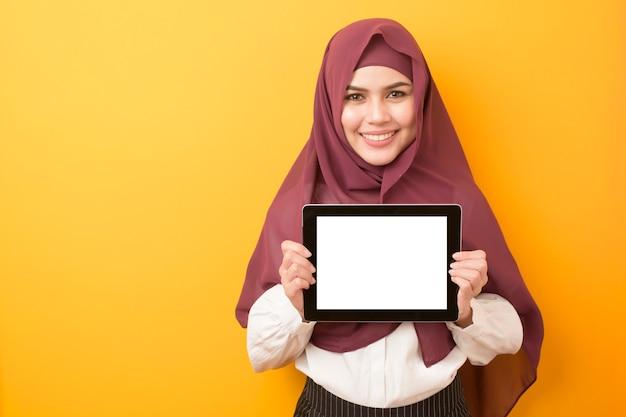Retrato de hermosa estudiante universitaria lleva hijab con maqueta de tableta sobre fondo amarillo