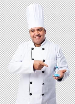 Retrato de un hombre cocinero que muestra su temporizador de arena