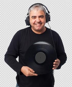 Retrato de un hombre maduro escuchando música y sosteniendo un vinilo.