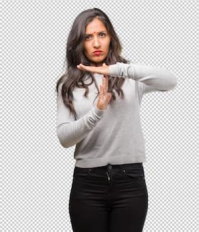 Retrato de joven india cansada y aburrida, haciendo un gesto de tiempo de espera, debe detenerse debido al estrés laboral, el concepto de tiempo