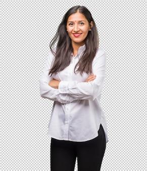 Retrato de una joven india cruzando los brazos, sonriente y feliz, confiada y amigable