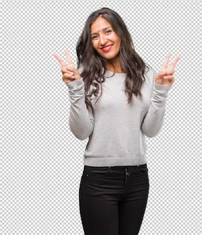 Retrato de una joven india divertida y feliz, positiva y natural, haciendo un gesto de victoria, concepto de paz