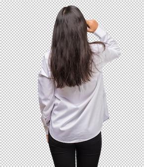 Retrato de joven india que muestra de nuevo, posando y esperando, mirando hacia atrás