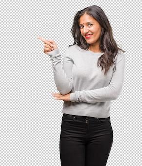 Retrato de joven mujer india apuntando hacia el lado