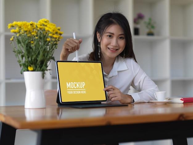 Retrato de mujer explicando su idea y mostrando maqueta de computadora portátil