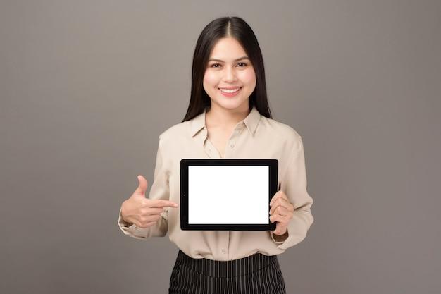 El retrato de la mujer hermosa joven está sosteniendo la maqueta de la tableta