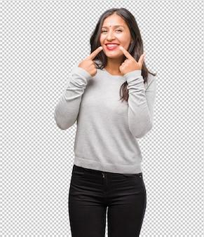 El retrato de la mujer india joven sonríe, señalando la boca
