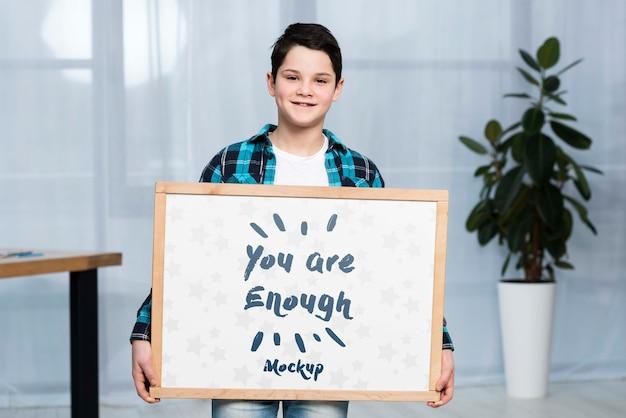 Retrato de niño positivo con cartel de maqueta