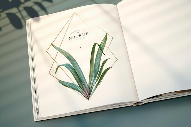 Revista maqueta con hojas y marco dorado.