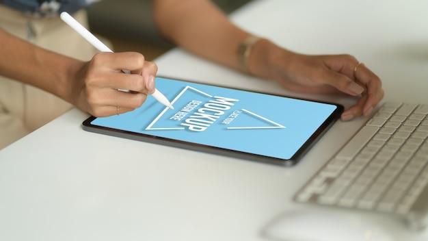 Ritagliata colpo di mano femminile disegno su mock up tablet con lo stilo sul tavolo del computer nella stanza dell'ufficio