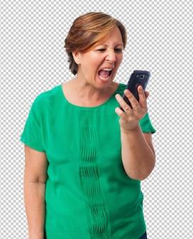 Ritratto della donna matura arrabbiata che parla sul telefono