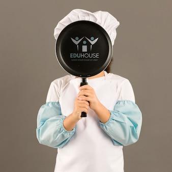 Ritratto della ragazza che posa come cuoco