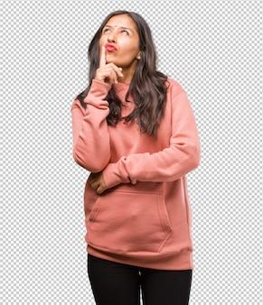 Ritratto di fitness giovane donna indiana, pensando e alzando lo sguardo, confuso su un'idea