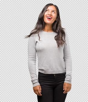 Ritratto di giovane donna indiana alzando lo sguardo, pensando a qualcosa di divertente e avere un'idea
