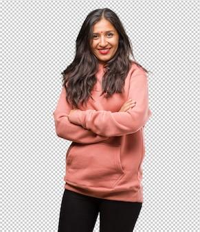 Ritratto di giovane donna indiana di forma fisica che attraversa le sue braccia, sorridente e felice, essendo sicuro e amichevole