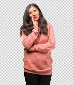 Ritratto di giovane donna indiana di forma fisica che dubita e confuso