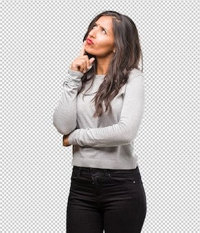 Ritratto di giovane donna indiana, pensando e alzando lo sguardo, confuso su un'idea